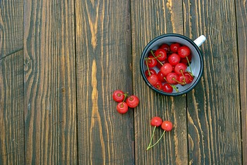 Cherry in enameled mug on a wooden background. Summer concept, copy space