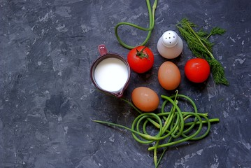 Ingredients for the preparation of an omelette with tomatoes and garlic arrows on a dark gray concrete background. Egg, fresh garlic arrows, tomatoes, milk, dill, salt