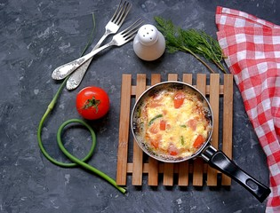 Lush omelette or frittata with garlic arrows and tomatoes in a portioned pan