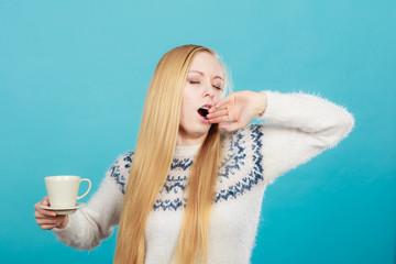 Sleepy woman holding cup of coffee