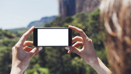Hipster blogger girl holds mobile phone in female hands, take photo picture of natural landscape on a sunny summer day while travel and vacation, clean blank screen cellphone closeup