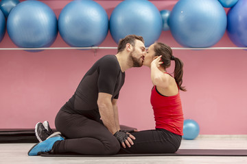 Young Couple Kissing in a Gym