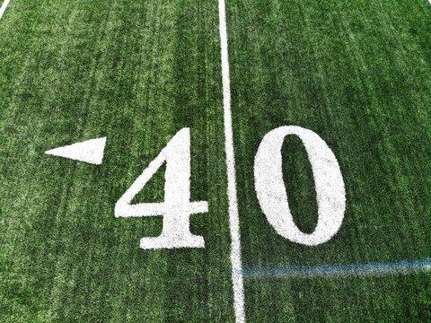 40 yard chalk mark on an green American football field taken from an aerial drone