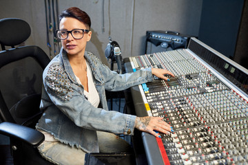 Stylish woman working with control console in music recording studio looking away in process.