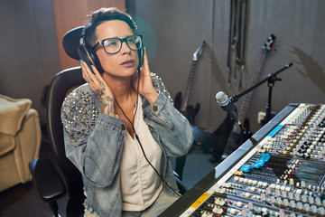 Trendy tattooed woman in headphones sitting at console in recording studio and looking away with concentration.
