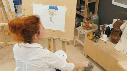 Ginger female artist using aquarelle to paint still life