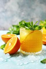 Cold summer orange lemonade with mint and ice cubes.