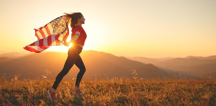 happy woman with flag of united states enjoying the sunset on nature