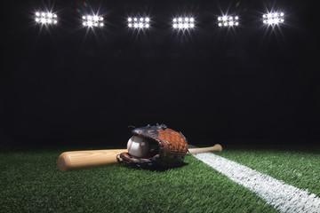 Baseball, mitt and bat on field below lights at night