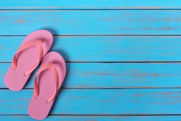 Pink flip flop sandals old summer beach wood background painted blue