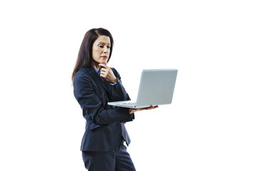 Portrait of an interested woman in business suit standing and looking at laptop, isolated on white studio background