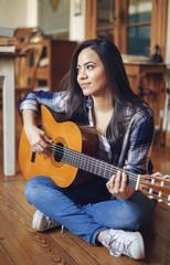hispanic young woman playing acoustic guitar