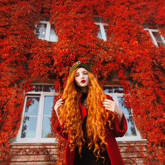 Young unusual pale girl with curly red hair on a autumn background. Beautiful redhead woman in a red coat and a green turban. Autumn bright look