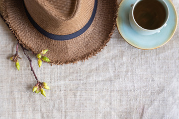 Top view of Summer brown panama straw hat with cup of tea and flower plant on linen cloth.travel concept.copy space for adding text.