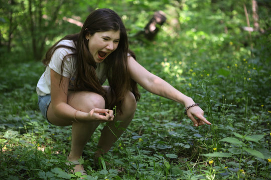 teenager girl shout see snake in the grass in forest close up photo