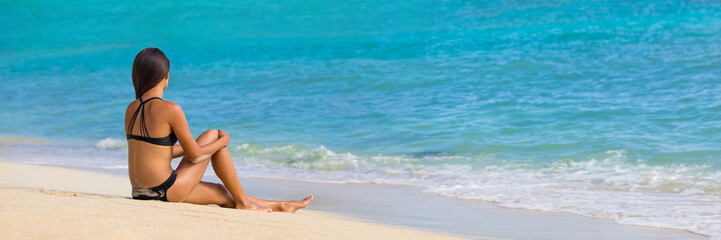 Summer beach vacation banner travel lifestyle woman. Tropical vacations bikini girl sitting down on white sand at holiday destination relaxing enjoying sun on holidays.