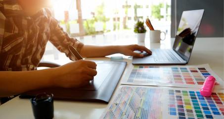 Artist or graphic designer working on digital tablet in studio office.