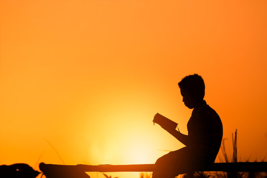 Boy reading holy bible on wood , christian silhouette concept.