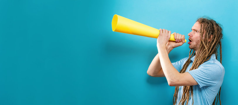 Young man holding a paper megaphone on a solid background