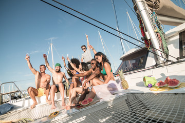 party in a yacht by group of young friends drinking champagne and toasting with raised glasses on a sunny day sitting on boat front