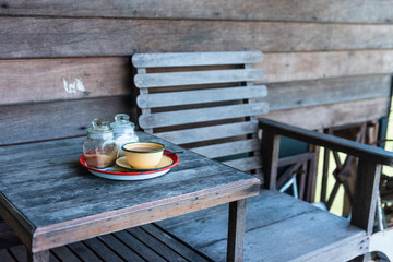 Traditional Thai coffee on wooden table and empty wooden chair