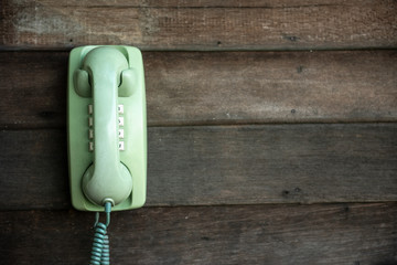Old green telephone on wooden wall