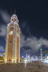 Old clock tower and skyline in Hong Kong city at night
