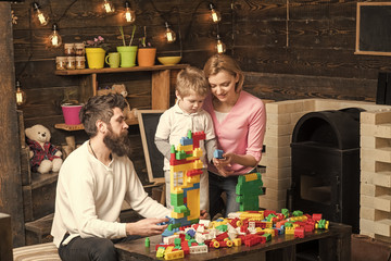 adoption of a child. Mom, dad and kid sitting around table with colorful construction bricks. Family building a house out of plastic blocks. Mother and son choosing pieces for constructing toy tower
