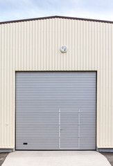 industrial warehouse exterior. closed gray metal gate with door