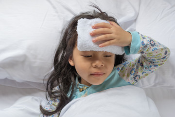 Little sick girl lying on bed with cool gel sheet on forehead