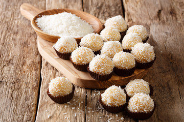 Authentic brazilian sweets beijinhos with condensed milk and coconut close-up. horizontal