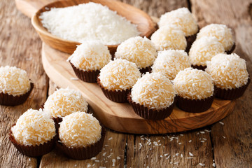 Appetizing candy balls beijinhos de coco with condensed milk and coconut close-up. horizontal