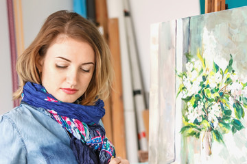 portrait of a girl painter with a palette of colorful paintings in an art studio. Thoughtful artist,