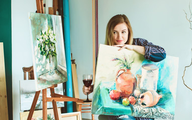 girl painter with a palette of colors and a glass of wine in an art studio. Palettes and easel,