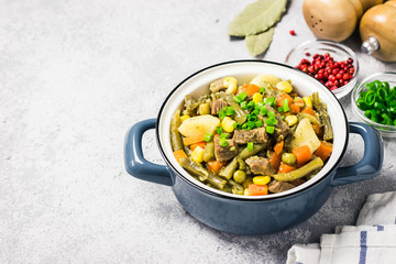 Vegetables and meat stew in a pot. Selective focus, space for text.