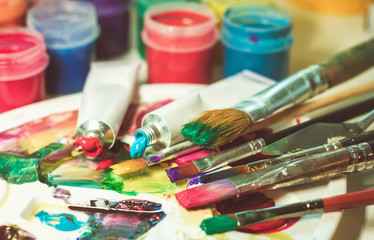 group of used brushes and a color palette. artist set of ideas of creative inspiration. a palette with paint and brushes
