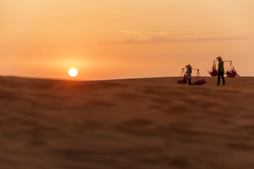 Woman carrying flower basket at sunset in Mui Ne sand dune, Vietnam