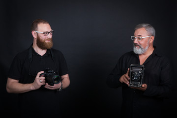 Two male photographers, young and elderly, with cameras - modern digital and vintage widescreen. On a black background in the studio.