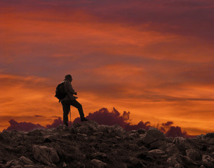 hiker on cliff of mountain at sunset