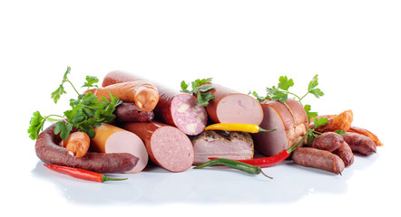 Different sausages and smoked meats isolated on white .