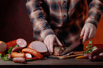 Man  cuts various sausages and smoked meat .