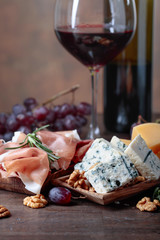 Glass of red wine with various cheeses , fruits and prosciutto .