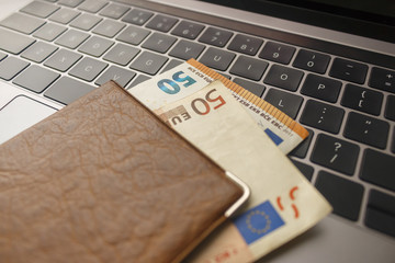 passport with euro banknotes lie on a black laptop keyboard