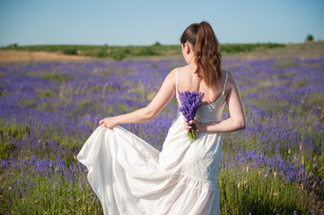 beautiful young female in white dress with flower bouquet in lavender summer meadows