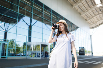 Young pretty traveler tourist woman in hat take pictures on retro vintage photo camera at international airport. Female passenger traveling abroad to travel on weekends getaway. Air flight concept.