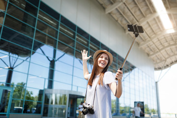 Young smiling traveler tourist woman with retro vintage photo camera doing selfie on mobile phone with monopod selfish stick at airport. Passenger traveling abroad on weekends. Air flight concept.