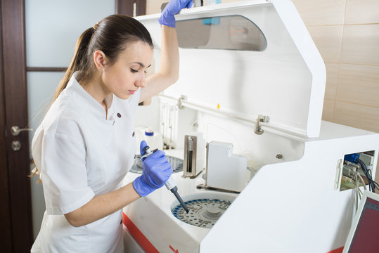 Young woman doctor or scientist working with a device for blood analysis