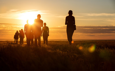 A group of people walking in a track. They go against the background of the orange sun, their contours and silhouettes are visible.