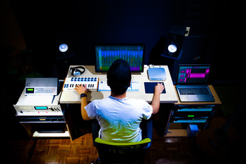 back of male asian producer arranging a song in home studio, music production technology concept