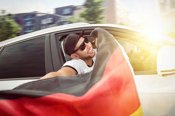 Fußballfan hält Deutschlandfahne aus dem Auto
